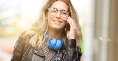 Young student woman with headphones happy talking using a smartphone mobile phone
