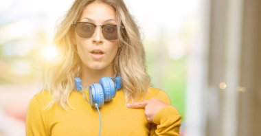 Young beautiful woman with headphones happy and surprised cheering expressing wow gesture, pointing with finger