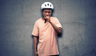 Black man wearing bike helmet sick and coughing, suffering asthma or bronchitis, medicine concept