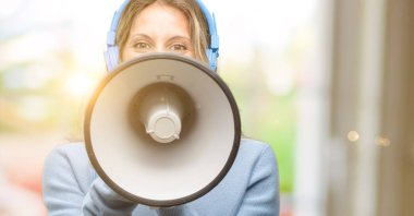 Young beautiful woman listening to music communicates shouting loud holding a megaphone, expressing success and positive concept, idea for marketing or sales