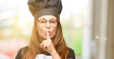 Middle age cook woman wearing chef apron with index finger on lips, ask to be quiet. Silence and secret concept