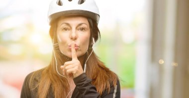 Middle age cyclist woman using earphones with index finger on lips, ask to be quiet. Silence and secret concept