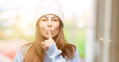 Middle age woman wearing wool winter cap with index finger on lips, ask to be quiet. Silence and secret concept