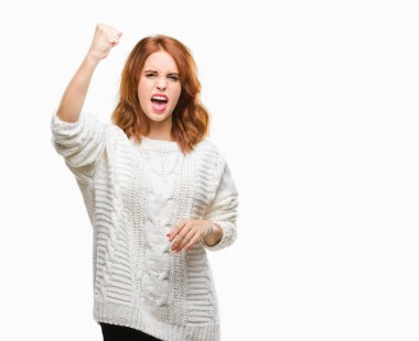 Young beautiful woman over isolated background wearing winter sweater angry and mad raising fist frustrated and furious while shouting with anger. Rage and aggressive concept.