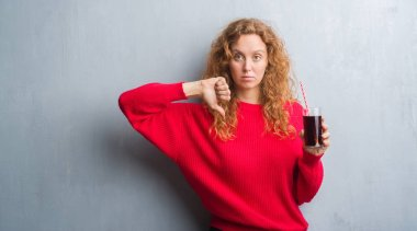 Young redhead woman over grey grunge wall drinking soda refreshment with angry face, negative sign showing dislike with thumbs down, rejection concept