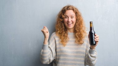 Young redhead woman over grey grunge wall holding beer bottle screaming proud and celebrating victory and success very excited, cheering emotion