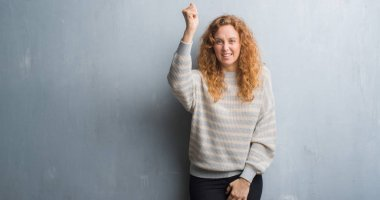 Young redhead woman over grey grunge wall angry and mad raising fist frustrated and furious while shouting with anger. Rage and aggressive concept.