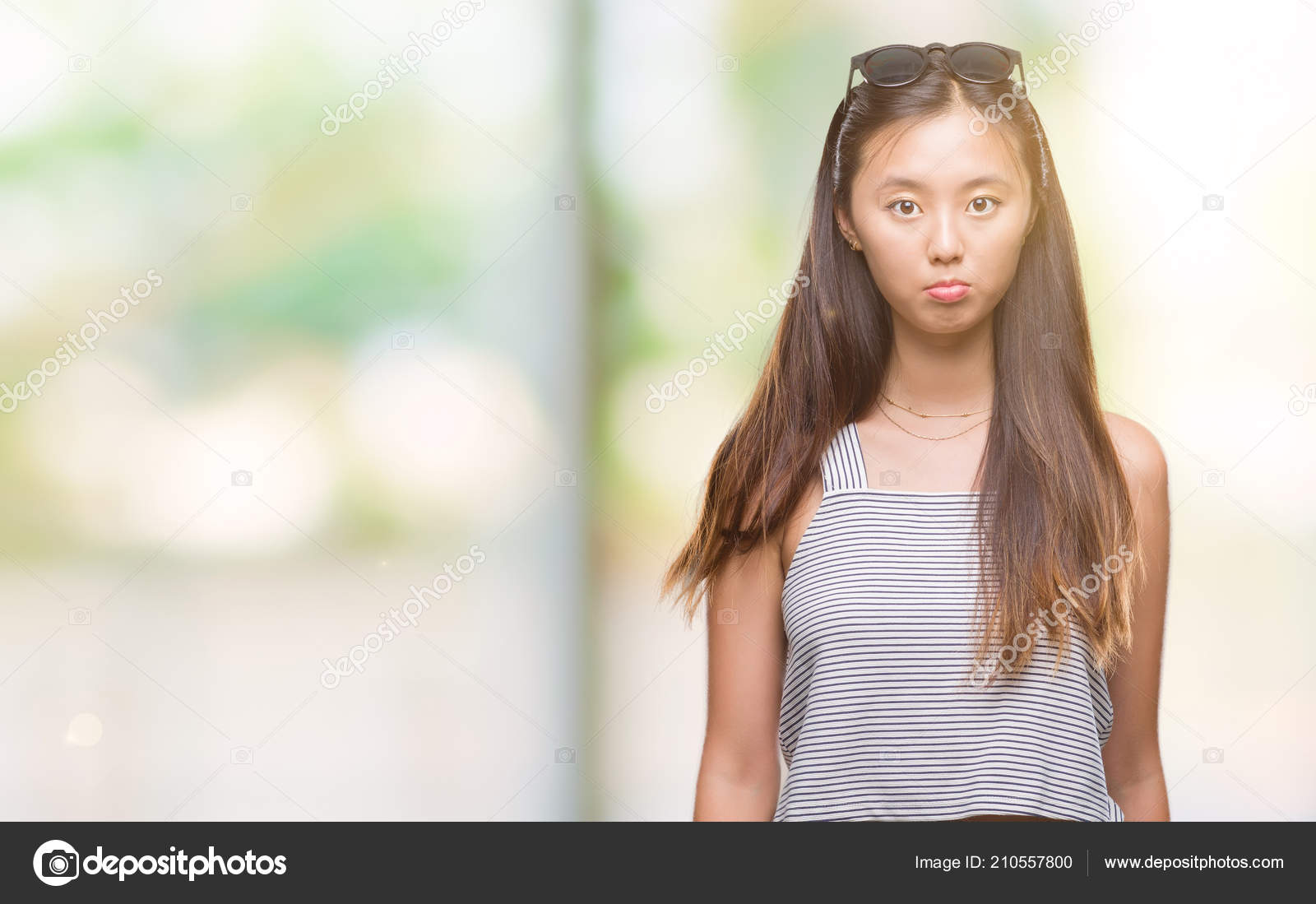 young asian woman wearing sunglasses isolated background depressed