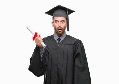Young handsome graduated man holding degree over isolated background scared in shock with a surprise face, afraid and excited with fear expression