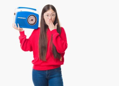 Young Chinese woman over isolated background holding vintage radio cover mouth with hand shocked with shame for mistake, expression of fear, scared in silence, secret concept