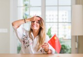 Photo Young woman at home holding flag of China stressed with hand on head, shocked with shame and surprise face, angry and frustrated. Fear and upset for mistake.