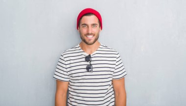 Handsome young hipster man over grey grunge wall wearing navy t-shirt and wool cap with a happy and cool smile on face. Lucky person.