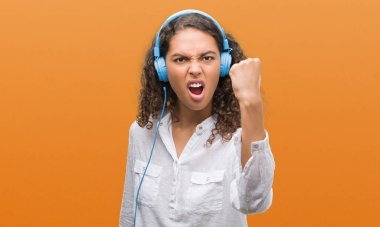 Young hispanic woman wearing headphones annoyed and frustrated shouting with anger, crazy and yelling with raised hand, anger concept