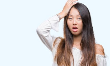 Young asian woman over isolated background surprised with hand on head for mistake, remember error. Forgot, bad memory concept.