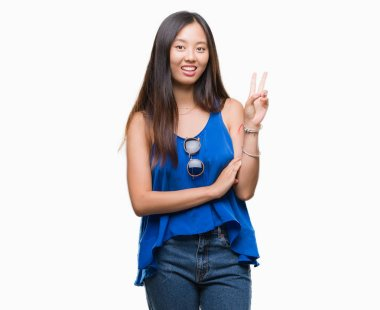 Young asian woman over isolated background smiling with happy face winking at the camera doing victory sign. Number two.