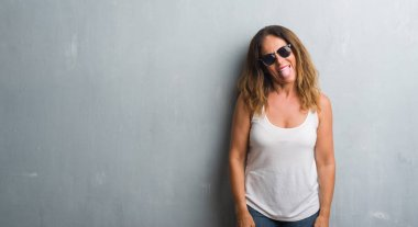 Middle age hispanic woman over grey wall wearing sunglasses sticking tongue out happy with funny expression. Emotion concept.