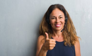 Middle age hispanic operator woman standing over grey grunge wall happy with big smile doing ok sign, thumb up with fingers, excellent sign
