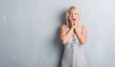 Adult caucasian woman over grunge grey wall wearing a dress scared in shock with a surprise face, afraid and excited with fear expression