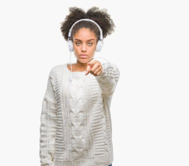 Young afro american woman wearing headphones over isolated background pointing with finger to the camera and to you, hand sign, positive and confident gesture from the front