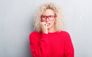 Young blonde woman with curly hair over grunge grey background looking stressed and nervous with hands on mouth biting nails. Anxiety problem.