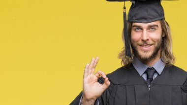 Young handsome graduate man with long hair holding degree over isolated background doing ok sign with fingers, excellent symbol