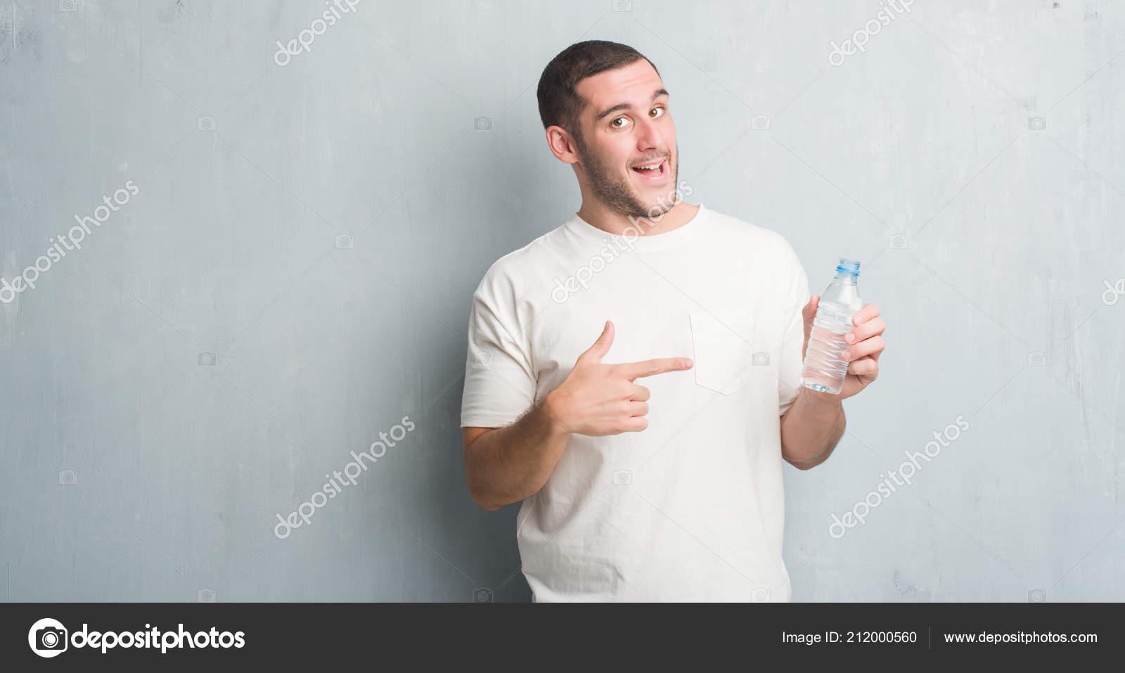 Hombre joven caucásico sobre pared gris grunge sosteniendo la botella de  agua muy feliz apuntando con la mano y del dedo — Foto de Aaron Amat b82dd000c6d5