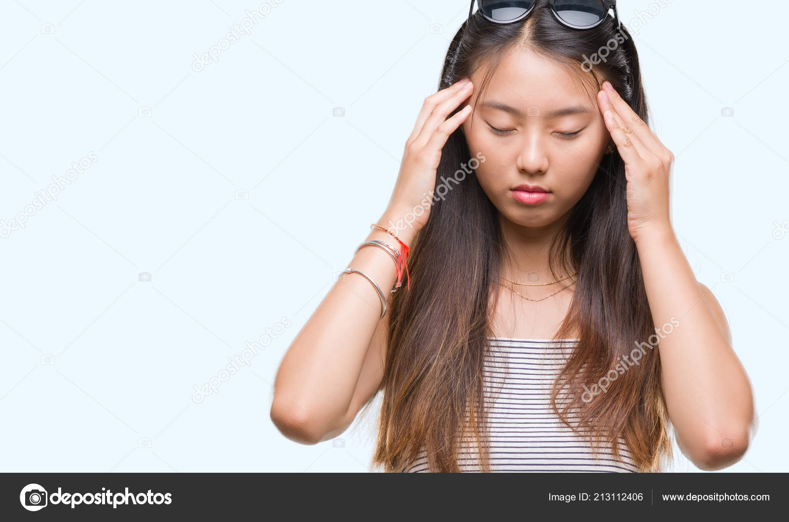 be03971de45 Young asian woman wearing sunglasses over isolated background with hand on  head for pain in head because stress. Suffering migraine.