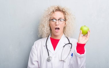 Young blonde dietitian doctor woman over grunge grey wall holding green apple scared in shock with a surprise face, afraid and excited with fear expression