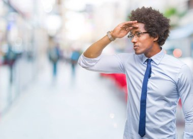 Afro american business man wearing glasses over isolated background very happy and smiling looking far away with hand over head. Searching concept.