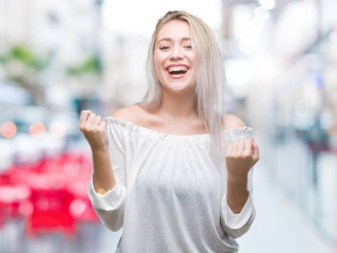 Young blonde woman over isolated background celebrating surprised and amazed for success with arms raised and open eyes. Winner concept.