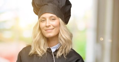 Beautiful cook woman chef confident and happy with a big natural smile laughing