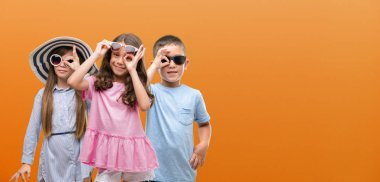 Group of boy and girls kids over orange background with happy face smiling doing ok sign with hand on eye looking through fingers