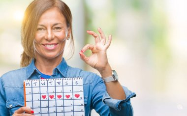 Middle age senior hispanic woman holding menstruation calendar over isolated background doing ok sign with fingers, excellent symbol