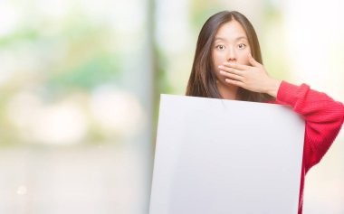 Young asian woman holding banner over isolated background cover mouth with hand shocked with shame for mistake, expression of fear, scared in silence, secret concept
