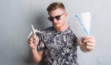 Young redhead man holding aircraf and boarding pass on holidays