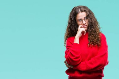 Beautiful brunette curly hair young girl wearing glasses and winter sweater over isolated background looking stressed and nervous with hands on mouth biting nails. Anxiety problem.