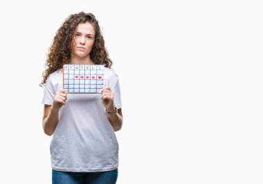 Young brunette girl holding menstruation calendar over isolated background with a confident expression on smart face thinking serious