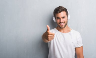 Handsome young man over grey grunge wall wearing headphones listening to music happy with big smile doing ok sign, thumb up with fingers, excellent sign