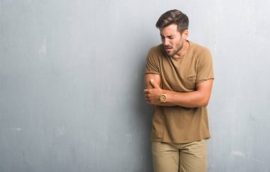 Handsome young man over grey grunge wall with hand on stomach because nausea, painful disease feeling unwell. Ache concept.