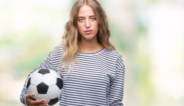 Beautiful young blonde woman holding soccer football ball over isolated background with a confident expression on smart face thinking serious