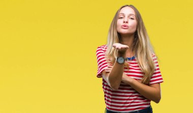 Young beautiful blonde woman over isolated background looking at the camera blowing a kiss with hand on air being lovely and sexy. Love expression.