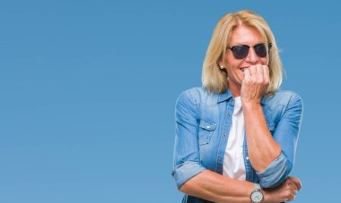 Middle age blonde woman wearing sunglasses over isolated background looking stressed and nervous with hands on mouth biting nails. Anxiety problem.