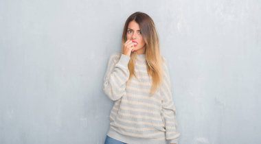 Young adult woman over grunge grey wall wearing winter sweater looking stressed and nervous with hands on mouth biting nails. Anxiety problem.
