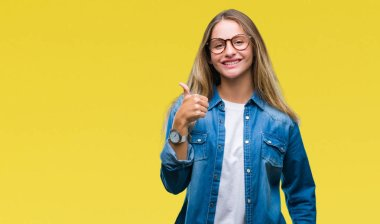 Young beautiful blonde woman wearing glasses over isolated background doing happy thumbs up gesture with hand. Approving expression looking at the camera with showing success.