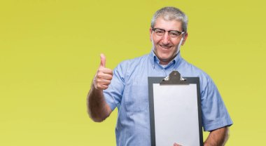 Handsome senior inspector man holding clipboard over isolated background happy with big smile doing ok sign, thumb up with fingers, excellent sign