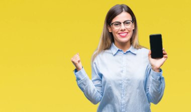 Young beautiful business woman showing blank screen of smartphone over isolated background screaming proud and celebrating victory and success very excited, cheering emotion