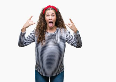 Beautiful brunette curly hair young girl wearing stripes sweater over isolated background shouting with crazy expression doing rock symbol with hands up. Music star. Heavy concept.