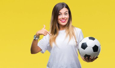 Young beautiful woman holding soccer ball over isolated background with surprise face pointing finger to himself