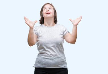 Young adult woman with down syndrome over isolated background crazy and mad shouting and yelling with aggressive expression and arms raised. Frustration concept.