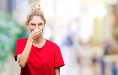 Young beautiful blonde woman wearing red t-shirt and glasses over isolated background smelling something stinky and disgusting, intolerable smell, holding breath with fingers on nose. Bad smells concept.